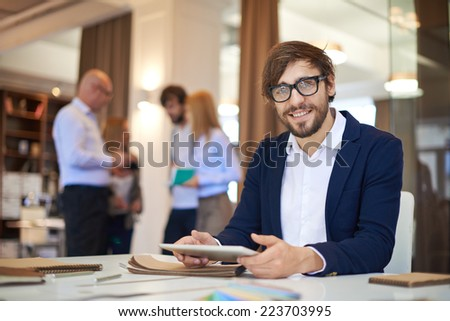 Modern businessman with touchpad looking at camera on background of his partners interacting - stock photo