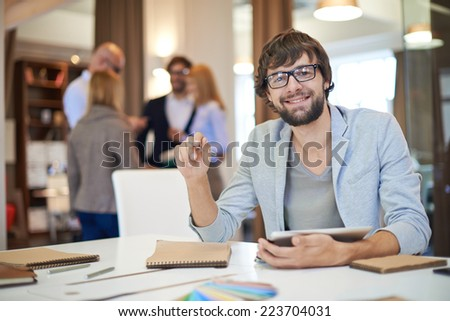 Modern businessman working in office on background of his partners interacting - stock photo