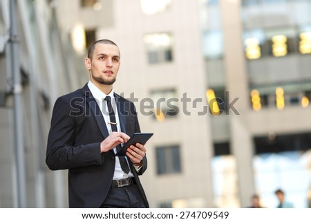 Modern businessman. Young man of arabic origin in a suit. Business man in the background office building. Confident businessman portrait. Confident, charismatic modern business man. Electronic tablet. - stock photo