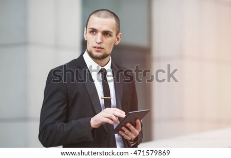 Modern businessman. Young man of arabic origin in a suit. Business man in the background office building. Confident businessman portrait. Confident, charismatic modern business man. Electronic tablet.