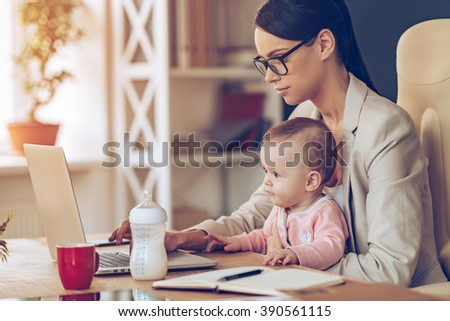 Modern businesswoman can manage everything. Side view of young beautiful businesswoman using laptop while sitting with baby girl on her knees at her working place - stock photo