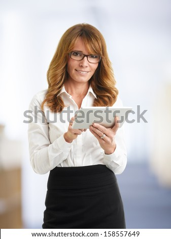 Modern businesswoman holding tablet in the office - stock photo
