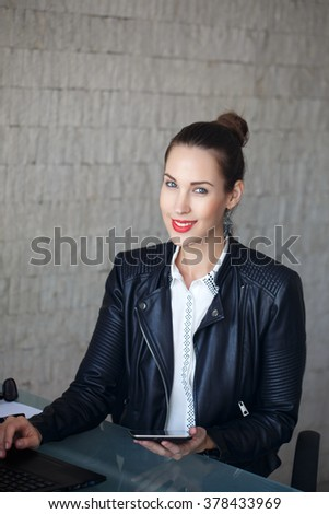 Modern businesswoman in leather jacket in office with tablet - stock photo