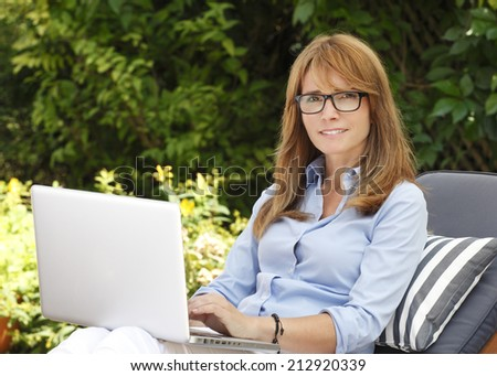 Modern businesswoman sitting at garden and working at home with laptop. Business people. - stock photo