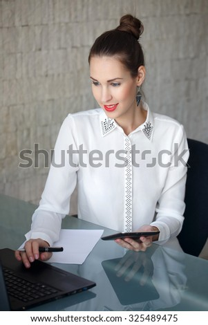 Modern businesswoman typing on laptop, red lips, in office - stock photo