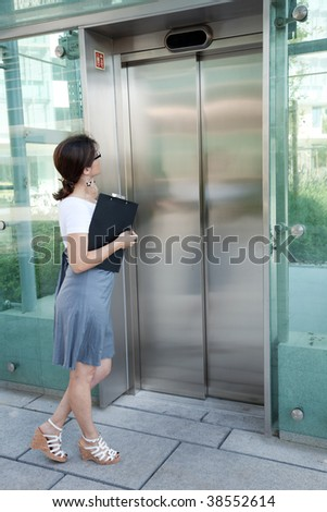 modern businesswoman waiting for the elevator - stock photo