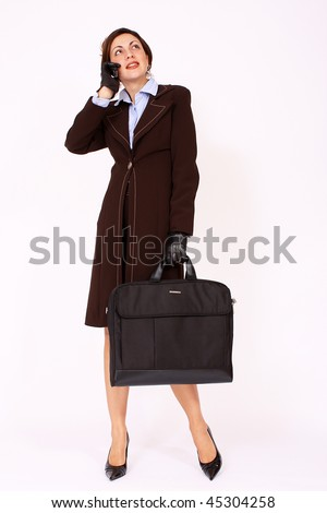 Modern businesswoman with briefcase speaking on the cell phone