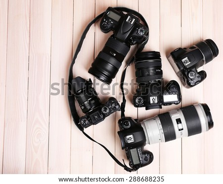 Modern cameras on wooden table, top view - stock photo