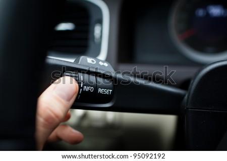 Modern car interior - driver pressing a button, using the car computer - stock photo