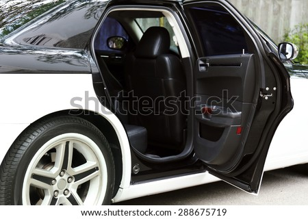 Modern car with open door outdoors - stock photo