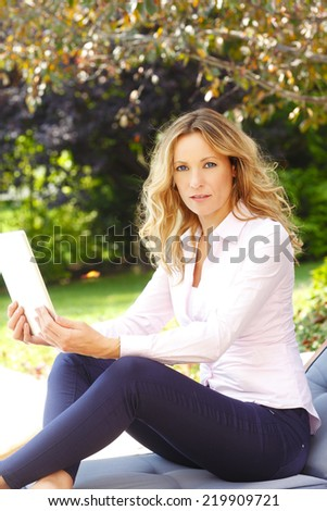Modern casual businesswoman relaxing at home while using digital tablet.  - stock photo