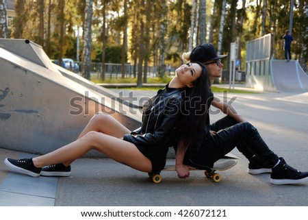 Modern casual couple posing with skateboard in skatepark.