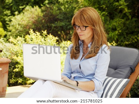 Modern casual woman sitting at garden with laptop, while writing her blog. Business people. - stock photo