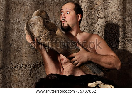 Modern caveman staring at mammoth femur bone - stock photo