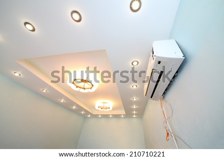 Modern ceiling with a lot of lights and air conditioner in the new apartment - stock photo