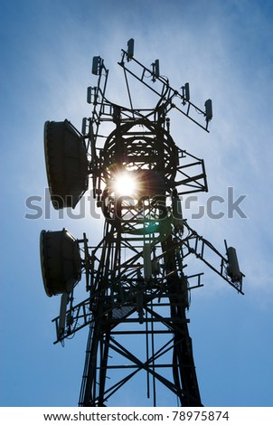 Modern cell and antenna with flat parabola on blue sky back lit by sun