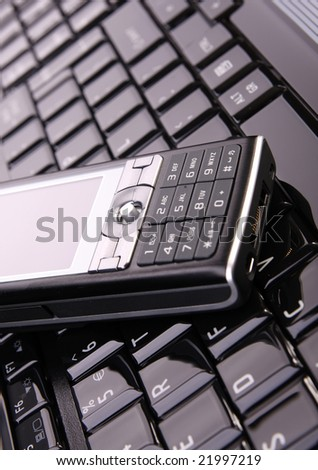 Modern cellphone on laptop keyboard