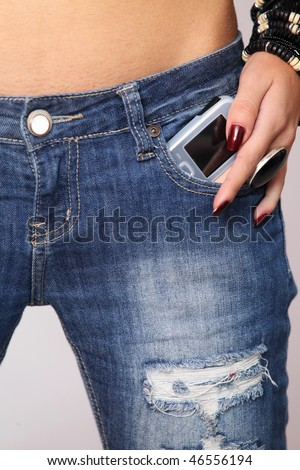 Modern cellphone sticking out of a jeans pocket - stock photo