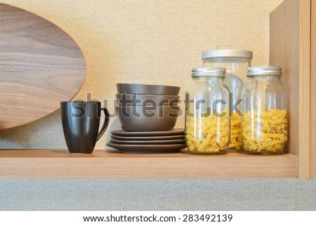 modern ceramic kitchenware and utensils on pantry shelf - stock photo