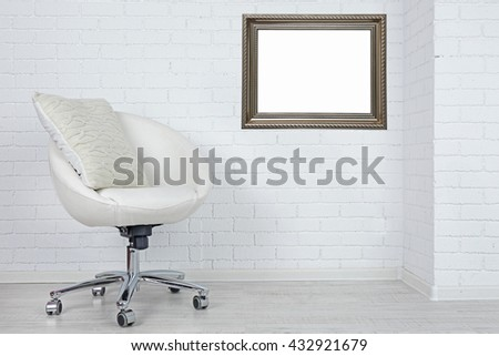 Modern chair with pillow and picture frame on white brick wall background - stock photo