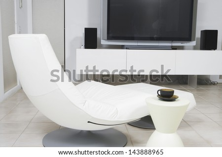Modern chair with tea cup in front of flat screen television in the living room - stock photo