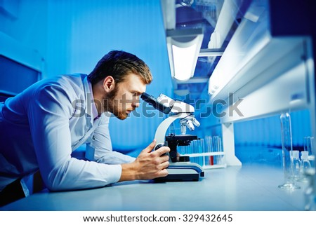 Modern chemist studying new microbiological substance in lab - stock photo