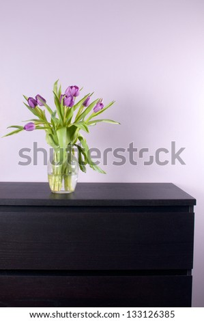 Modern chest drawer, purple tulips and lilac walls - stock photo