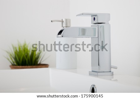 Modern chrome metal tap fitting in a bathroom mounted on a hand basin with a container of liquid soap and green leafy houseplant with focus to the faucet - stock photo