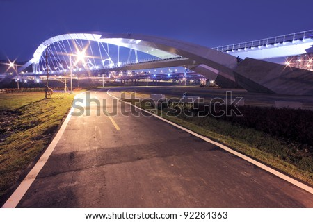 Modern City--a bike road going under a modern bridge of the express way in a cloudy evening - stock photo