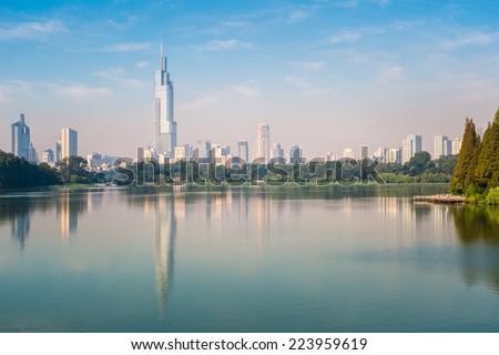 modern city building reflected in beautiful nanjing xuanwu lake - stock photo