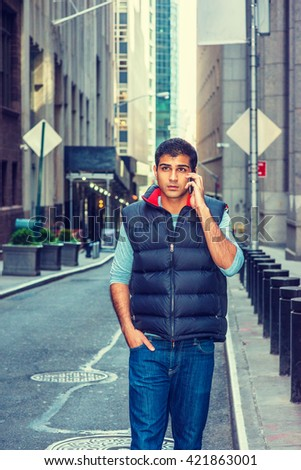 Modern City Life. East Indian American College Student wearing long sleeve T shirt, blue down vest, jeans, walking on narrow street in New York, talking on cell phone. Instagram filtered effect.  - stock photo