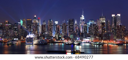 Modern City night scene. New York City Manhattan skyline panorama at night over Hudson River with refelctions viewed from New Jersey
