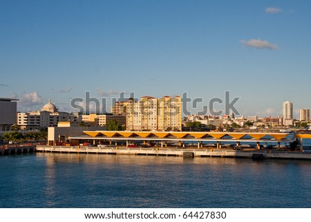 Modern city of San Juan Puerto Rico beyond empty berths at the shipping pier - stock photo