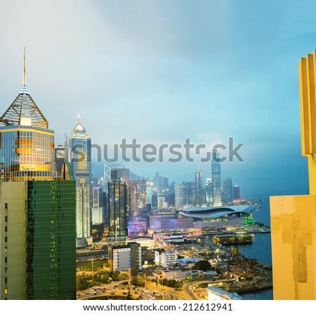 Modern city skyline at night against sunset sky. - stock photo
