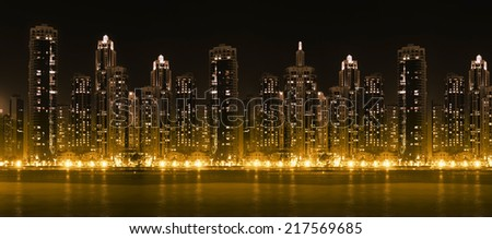 Modern city skyline at night with illuminated skyscrapers over water surface - stock photo