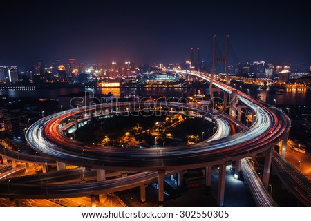 Modern city traffic road at night. Transport road junction on the bridge. road bridge night, road bridge on light, road junction shanghai, road bridge city, road junction curve, road bridge way - stock photo