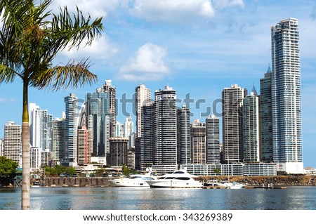 Modern city view - skyscrapers, luxurious yachts and coconut palm with water reflection - Panama City - stock photo
