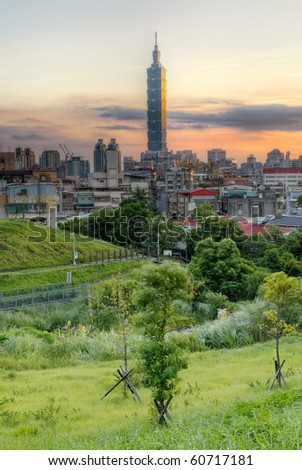 Modern city with green park grassland and dramatic sunset color in Taipei, Taiwan. - stock photo