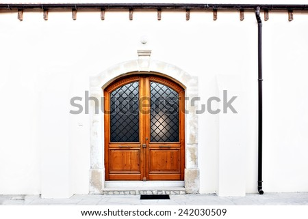 Modern classic wooden door with 2 wings, glass. Mediterranean Europe style. White walls with black pipe. Stone entry - stock photo