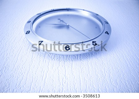 Modern clock on wall. Blue tint and wide angle. - stock photo
