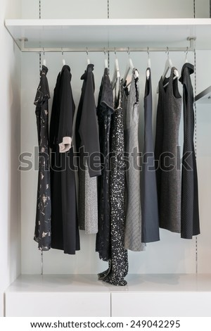 modern closet with row of black dress hanging on coat hanger in wardrobe. - stock photo