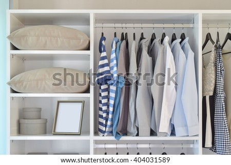 modern closet with row of cloths hanging in white wardrobe - stock photo