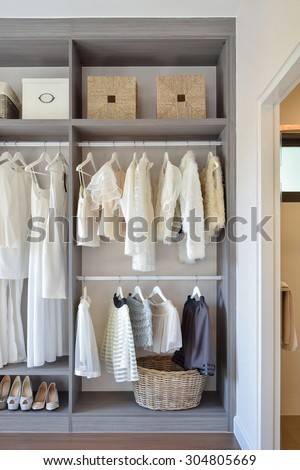 modern closet with row of white dress and shoes hanging in wardrobe - stock photo