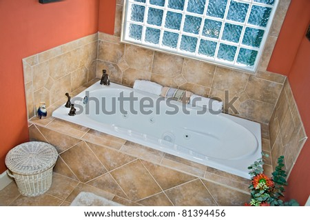 Modern colorful bathroom jacuzzi tub area with Travertine tile and bronze fixtures.