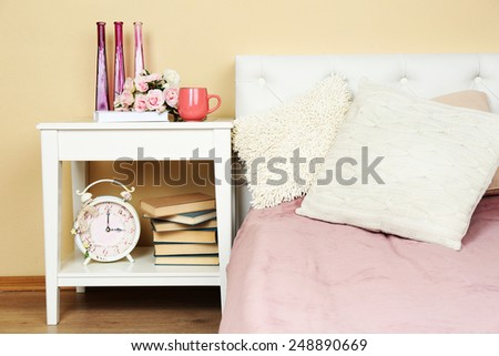 Modern colorful bedroom interior with bed and nightstand, with design details on light wall background - stock photo