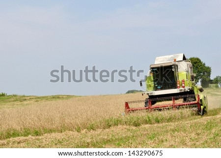 Modern combine in the field during harvesting with space on left side. Agriculture and Farming Collection. - stock photo