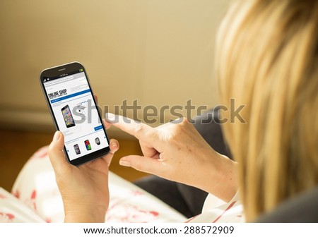 modern comerce or lifestyle concept:  woman with 3g generated smartphone with online shop interface on the screen. All screen graphics made up. - stock photo