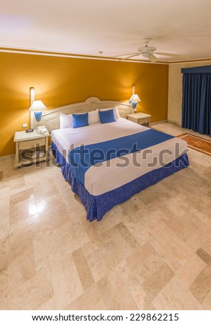 Modern comfortable and elegant master bedroom in a luxury mexican, caribbean  resort hotel. Interior design. Vertical. - stock photo