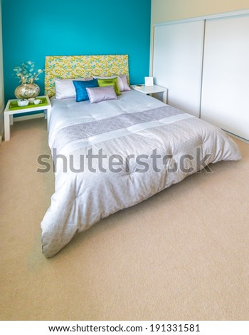 Modern comfortable, nicely decorated bedroom painted in blue Interior design. Vertical. - stock photo