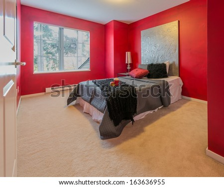 Modern comfortable, nicely decorated, bedroom painted in red. Interior design. - stock photo